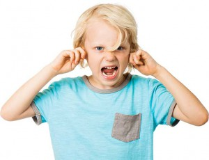 A photograph of a young boy screaming and plugging his ears
