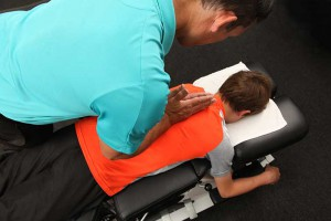A photograph of a chiropractor adjusting a young boy.