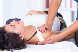 A photograph of a woman lying on a table, getting a shoulder adjustment